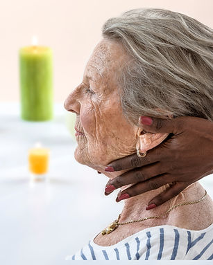Elderly woman receiving a neck massage from a masseuse in a brightly lit relaxing room