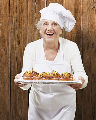 Senior woman wearing chef clothes carrying a platter of chocolate chip muffins