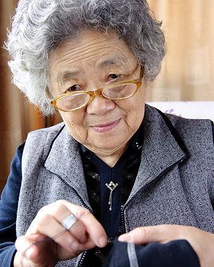 Senior citizen sewing a shirt