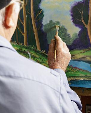 Senior citizen painting a picture
