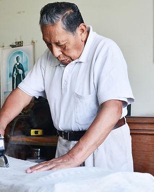 Elderly man ironing clothing
