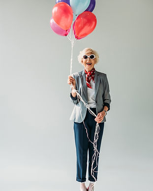 stylish senior lady wearing a blazer and scarf with sunglasses