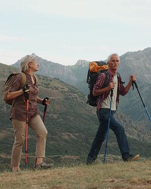 Active senior couple hiking in mountainous terrain