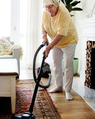 Senior woman vacuuming a rug