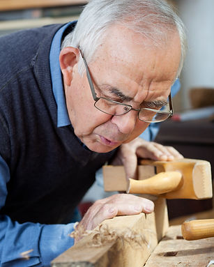 Senior man blowing shavings off of a freshly sanded piece of lumber