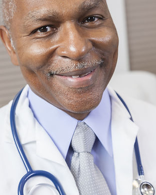 A senior male doctor smiling with a stethoscope around his neck