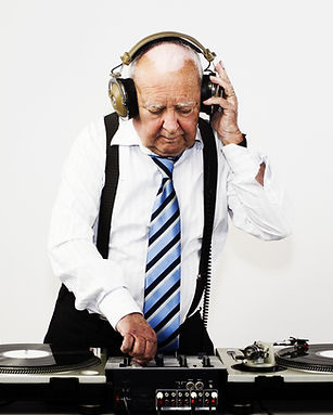 a very funky elderly man working as a disc jockey wit large headphones on