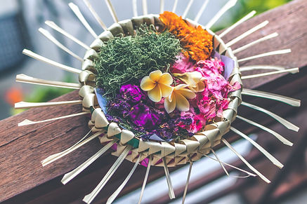 An Indonesian cultural offering of flowers and greenery in a decorative woven bamboo container