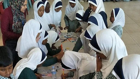 Young Muslim Indonesian students working on a task at a table with their teacher looking on