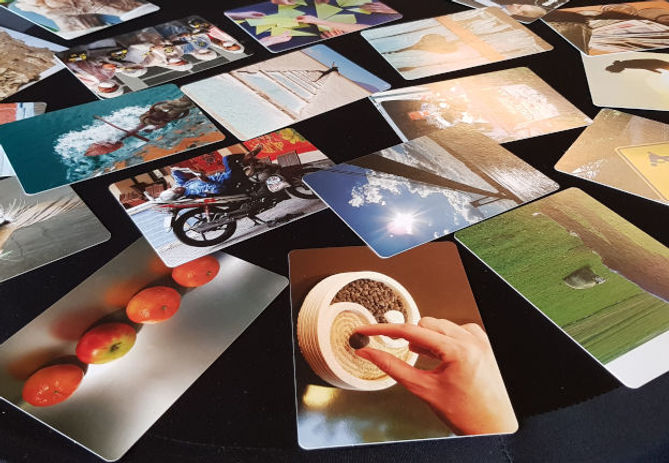A set of colourful picture cards scattered randomly across a black tabletop