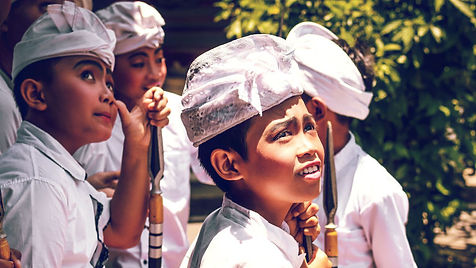 Four Indonesian boys in white ceremonial shirts and head dress looking up