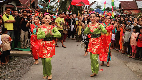 AIYEP participants in ceremonial dress lead a parade through a village street lined with people