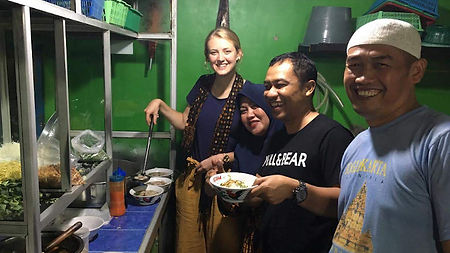 An Australian AIYEP participant serving bowls of food in a warung with three Indonesian people