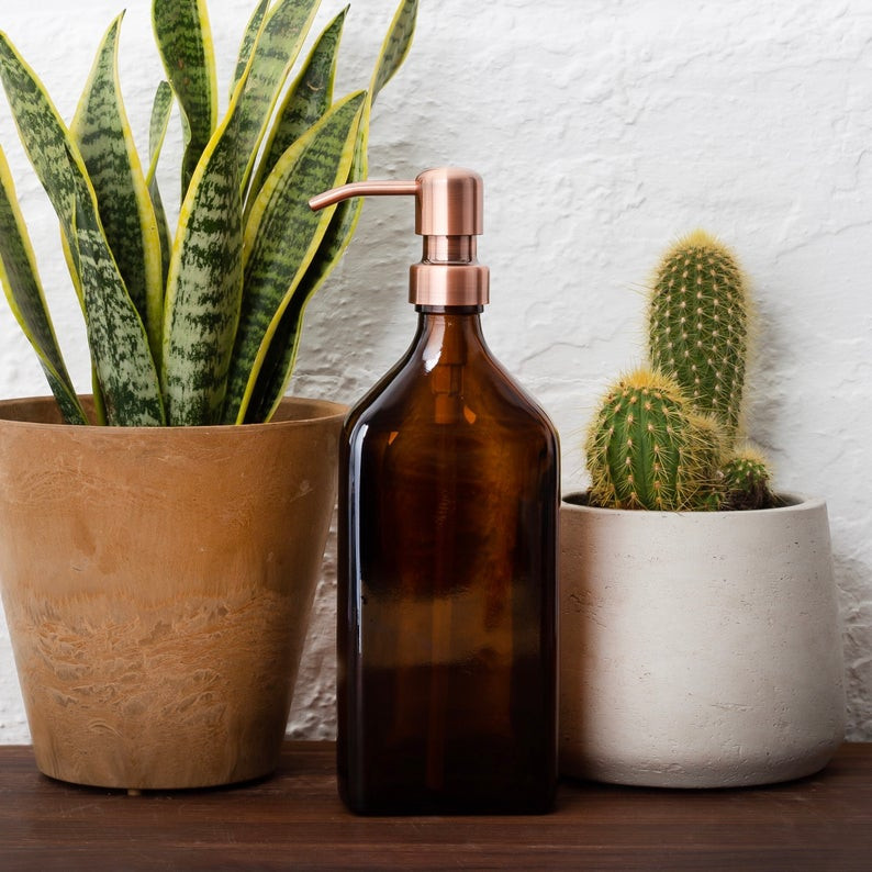 recyclable amber glass soap dispenser, made by Kuishi Home, with a cactus and mother-in-law tongue plant. To shop the soap dispenser click on the image and it will take you to Etsy shop.