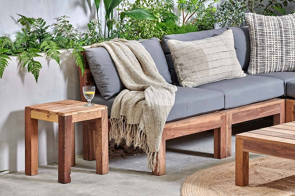 light wood L-shape outdoor sofa with grey seating cushions.