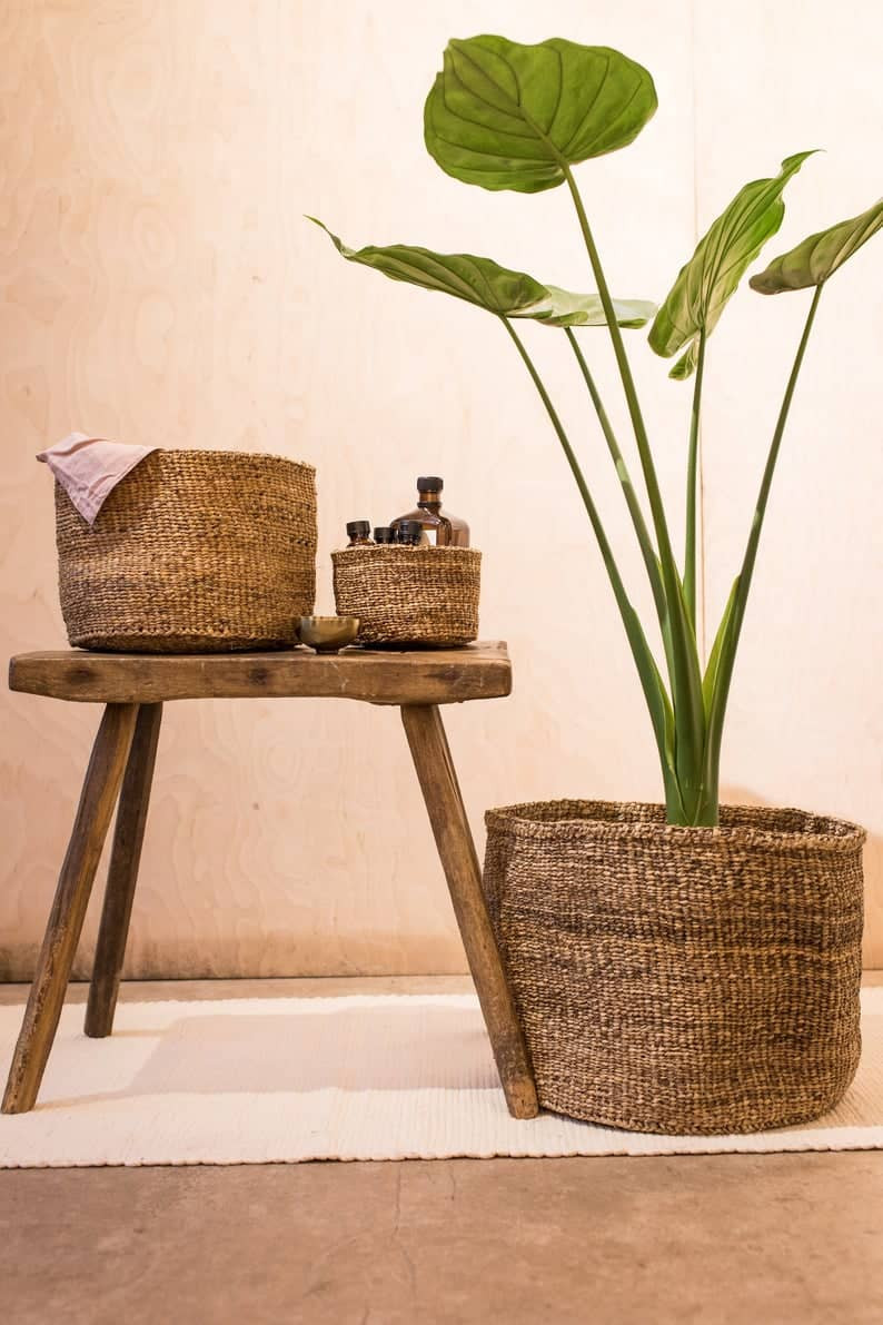 Handwoven basket made from banana tree fibres with monstera plant, next to tv stand. Click on the image to shop the basket on Etsy.