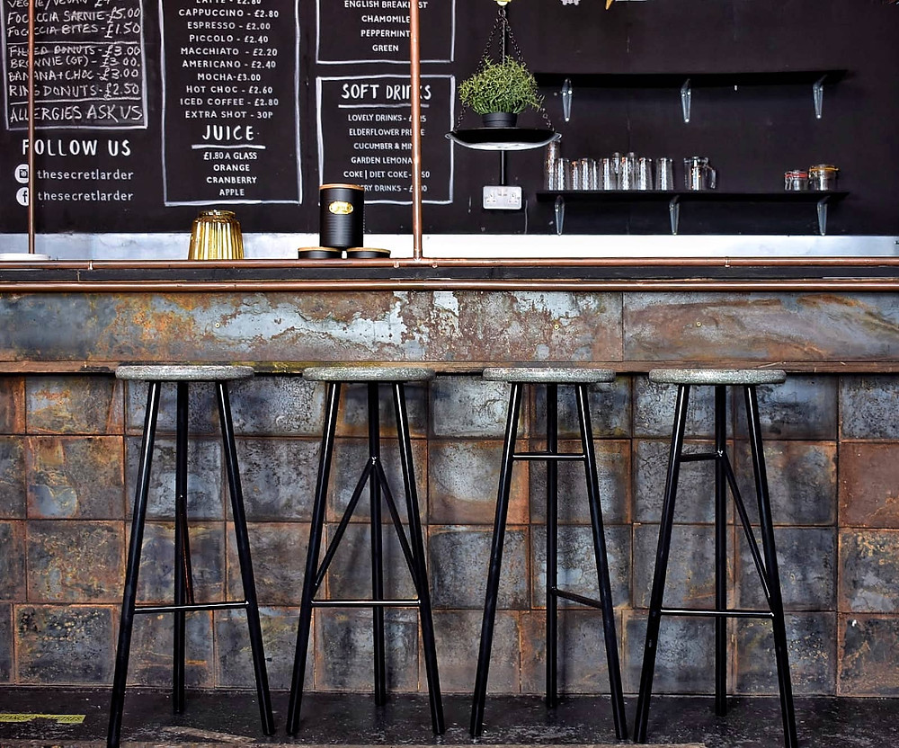 Industrial style sustainable bar stools made of recycled material with black metal legs.