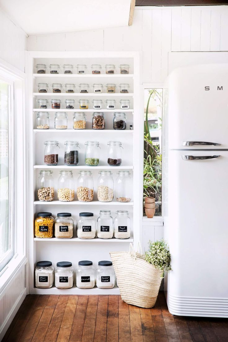 organised white kitchen shelving with glass containers and jars as spice holders.