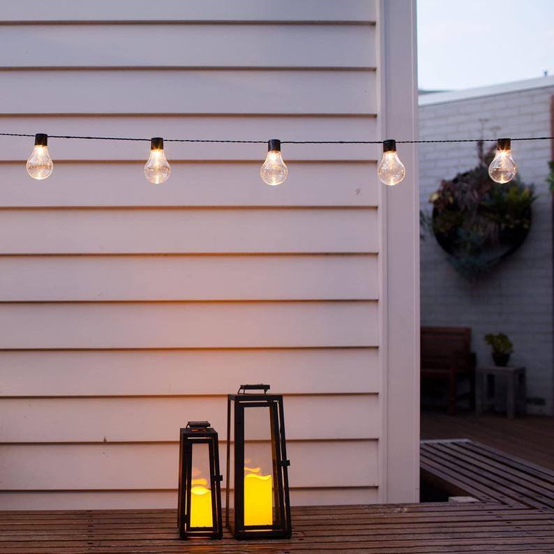 solar powered string lights hanging in front of white wall