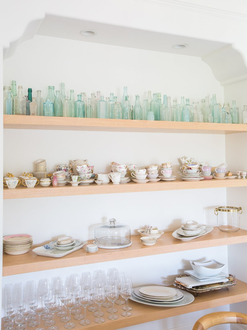 Open shelves in a kitchen filled with colourful china, plates and green glass bottles