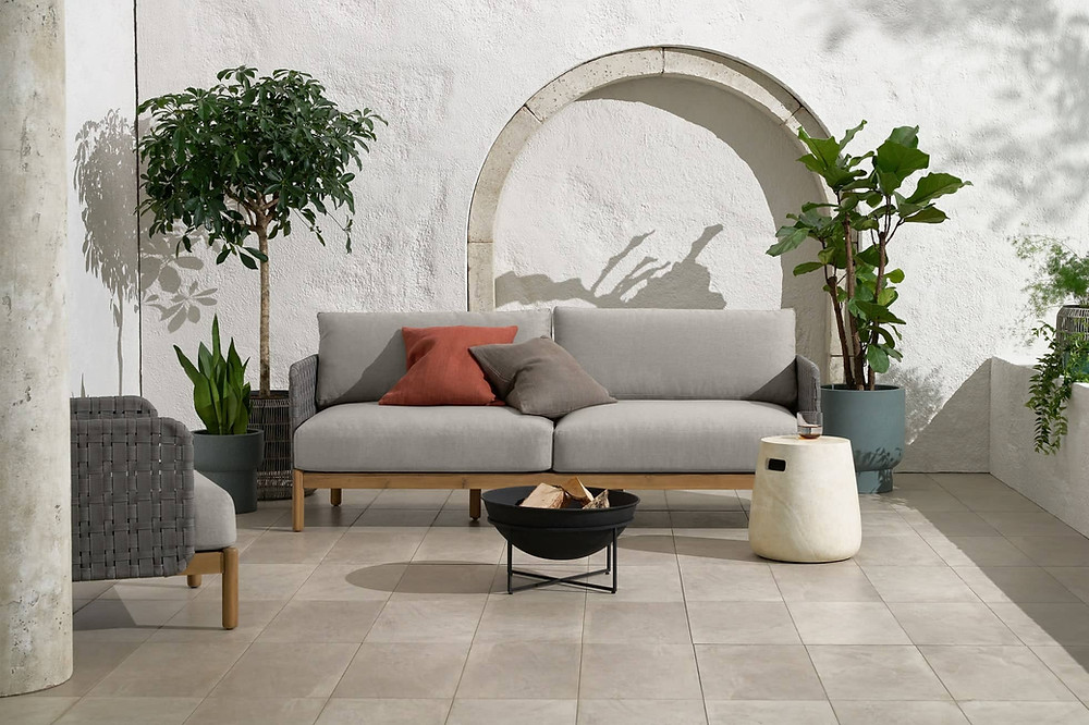 Light wood 3 seater outdoor sofa with cosy light grey seating cushions.