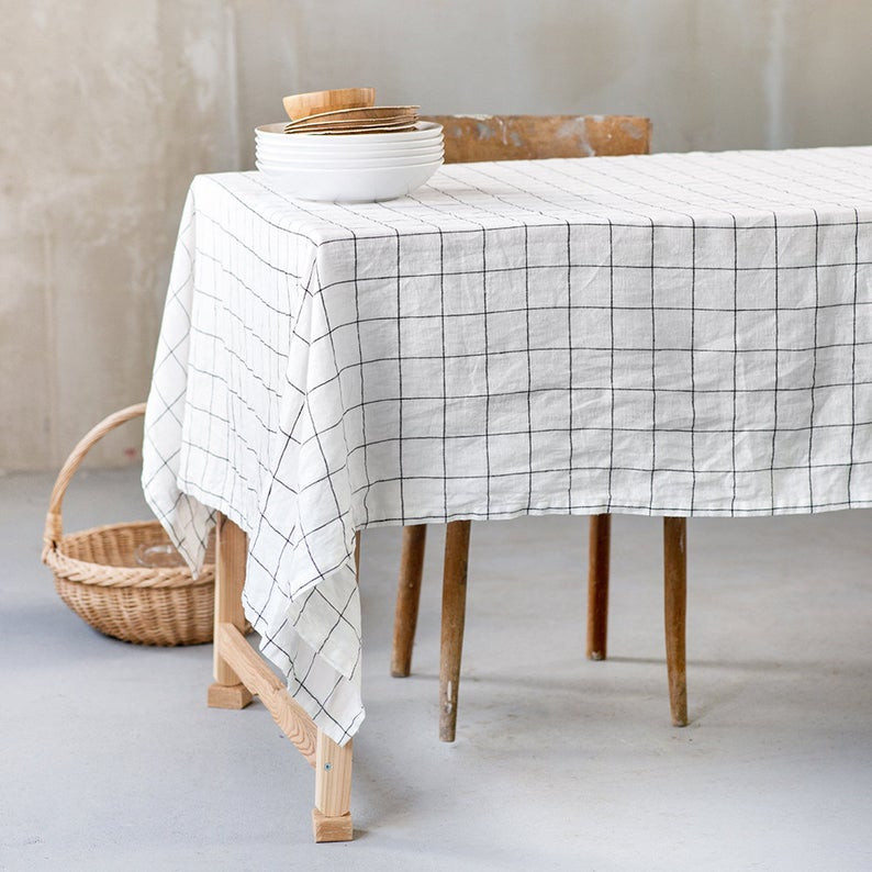 White natural linen tablecloth in large checks style, on a wooden table. Staged beautifully with a wooden chair and a wicker basket on the floor. To purchase this tablecloth clock on the image and it will take you to the Etsy shop called Not Perfect Linen.