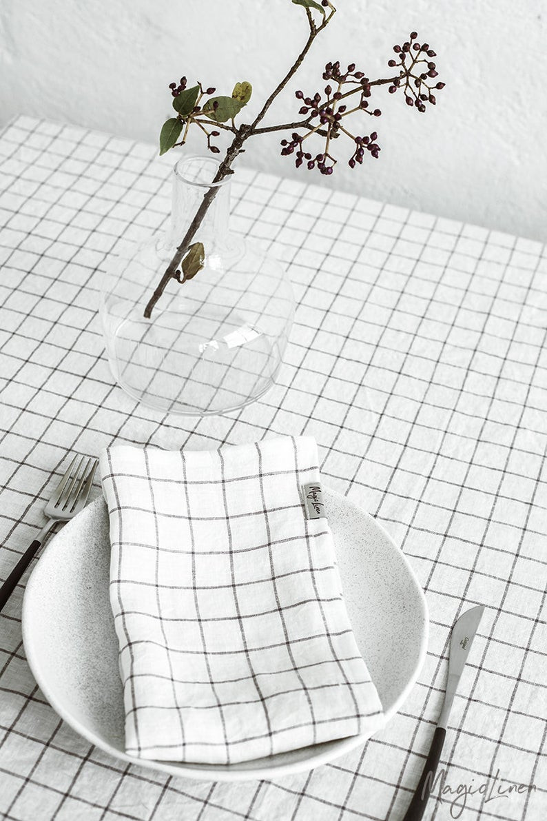 Eco-Friendly  reusable linen kitchen cloth white with large black check style lines, laid on a white plate and a  glass vase next to it. To get these napkins simply click on the image and it will take you to the Magic Linen Shop on Etsy.