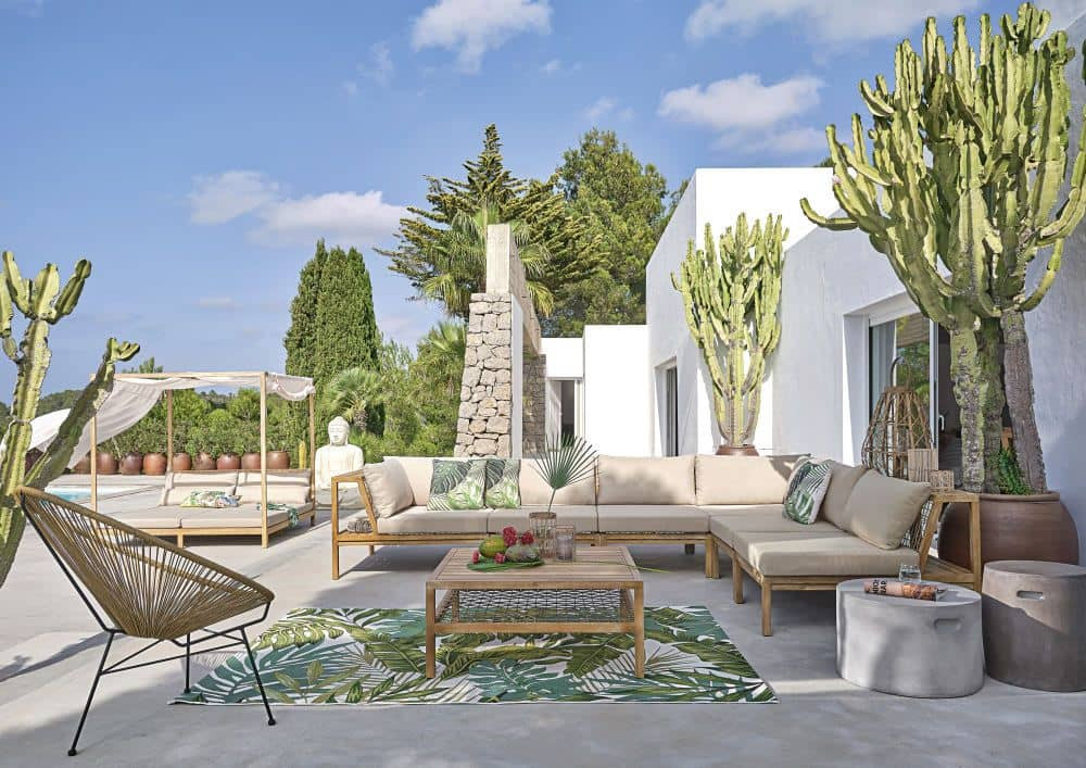outdoor living room with beige corner sofa, light wood coffee table, leafy print outdoor rug, concrete side table and a lounge chair