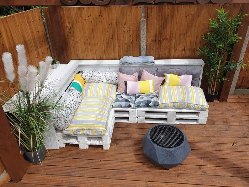 garden pallet furniture in white, decorated with colourful cushions