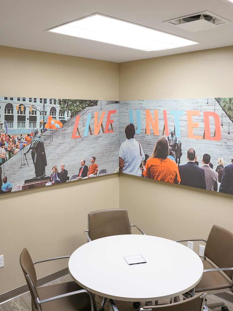 United Way of the Midlands mural created by Penny & Lucy Lou Art via photos provided from United Way day at the South Carolina State House. Art is printed with UV cured inks on acoustical fabric that is woven with a Boucle texture. This particular type of fabric has microscopic holes allowing the sound to travel to the fiberglass panels absorbing the sound.
