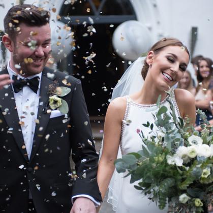 bride and groom walk under the confetti
