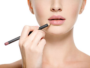 Girl apply lipstick with cosmetic penci