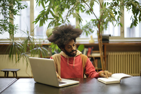 man-using-his-laptop-and-book-for-resear