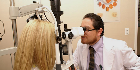 Image of Dr William Olivos performing an eye exam
