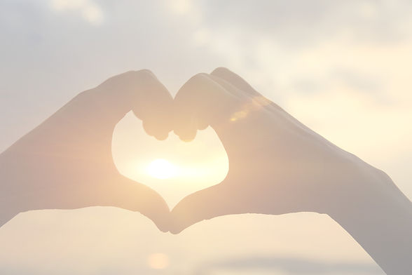 Heart%20shape%20making%20of%20hands%20against%20bright%20sea%20sunset%20and%20sunny%20golden%20way%2