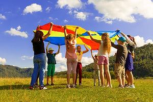 Kids holding a parachute outside