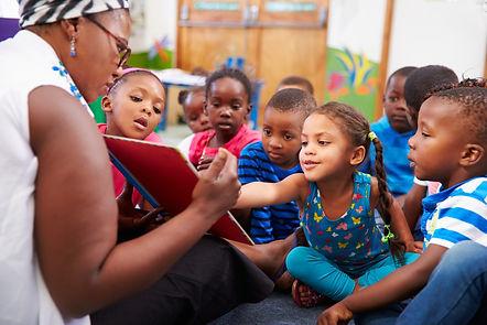 Teacher reading a book with a class of preschool children.jpg