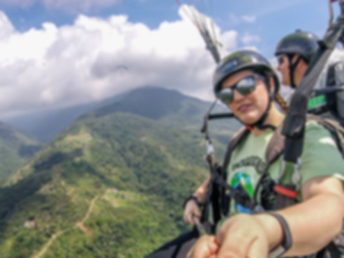 Girl tandem paragliding over Cauca Valley Colombia
