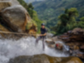 man rapelling down a waterfall