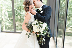 a green and white bouquet between a couple almost kissing
