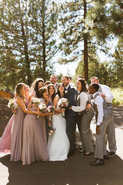 a sunny outside Oregon wedding party smiles around the bride and groom