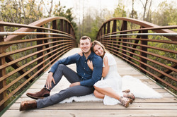 couple snuggled together smiling on bridge in memphis tn