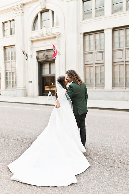 Wedding couple kissing in front of the Cadre Building in Downtown Memphis