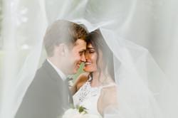 A couple snuggles under a wedding veil
