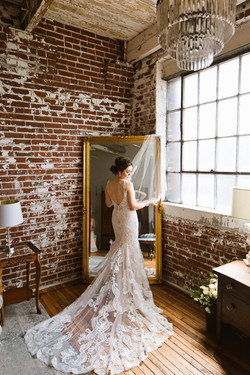 A bride stands in front of a mirror at 409 South Main