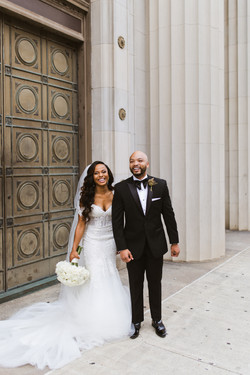 A bride and groom smile outside of The Cadre Building in downtown Memphis