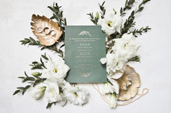 flatlay wedding invitaton with florals and gold accent leaves