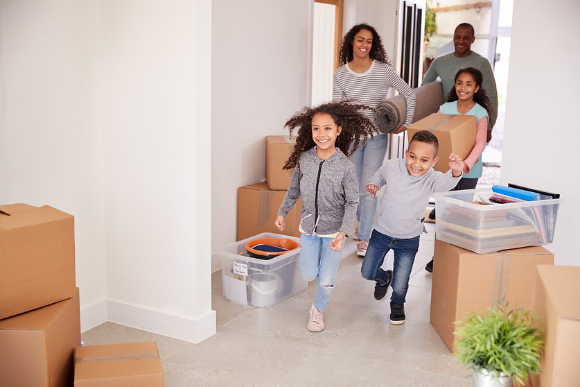 smiling-family-carrying-boxes-into-new-h