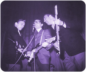 """L-R: Waylon Jennings, Buddy Holly, Tommy Allsup with drummer Carl """"Goose"""" Bunch"""