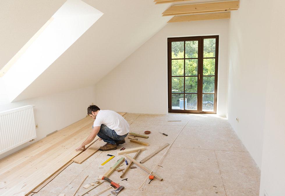 handyman installing flooring in the upstairs deck room in home.